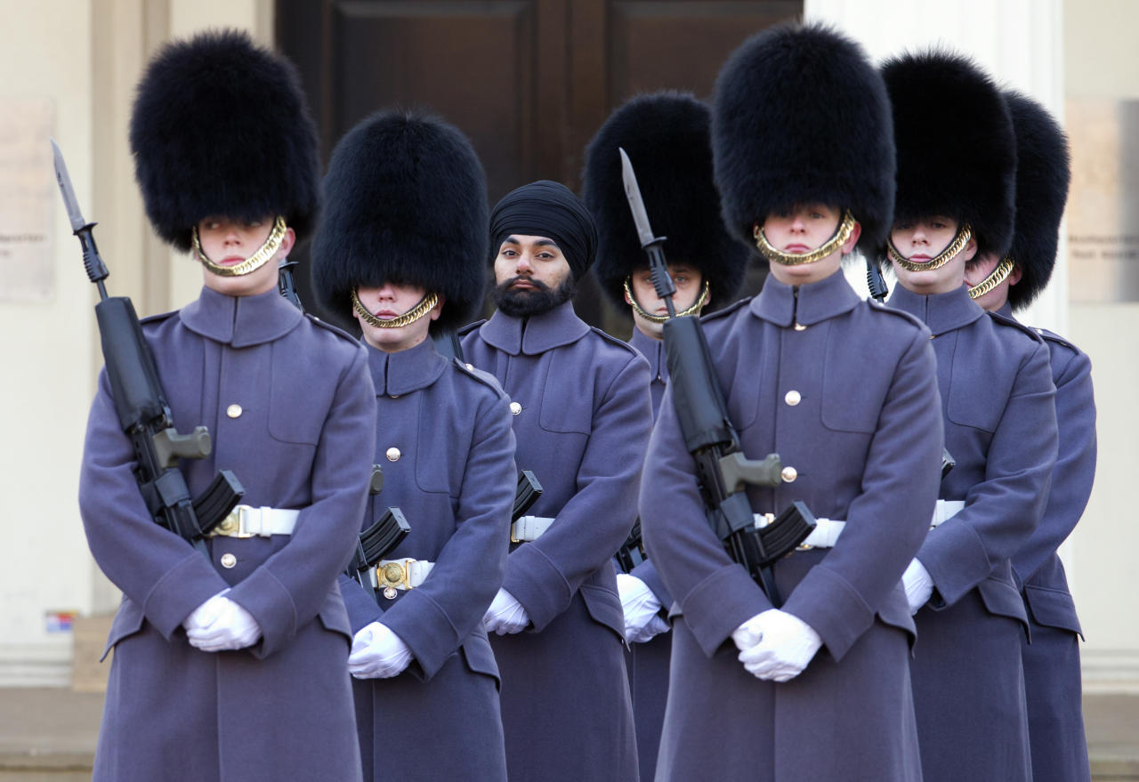 Sikh Guardsman Jatenderpal Singh Bhullar (C), a soldier in the Scots Guards, forms up with his fellow soldiers on the parade ground of Wellington Barracks before going on guard duty in the forecourt of Buckingham Palace on December 11, 2012 in London, England.  Guardsman Bhullar is the first Sikh Guardsman to wear a turban rather than the traditional bearskin whilst on guard duty. (Photo by Indigo/Getty Images)