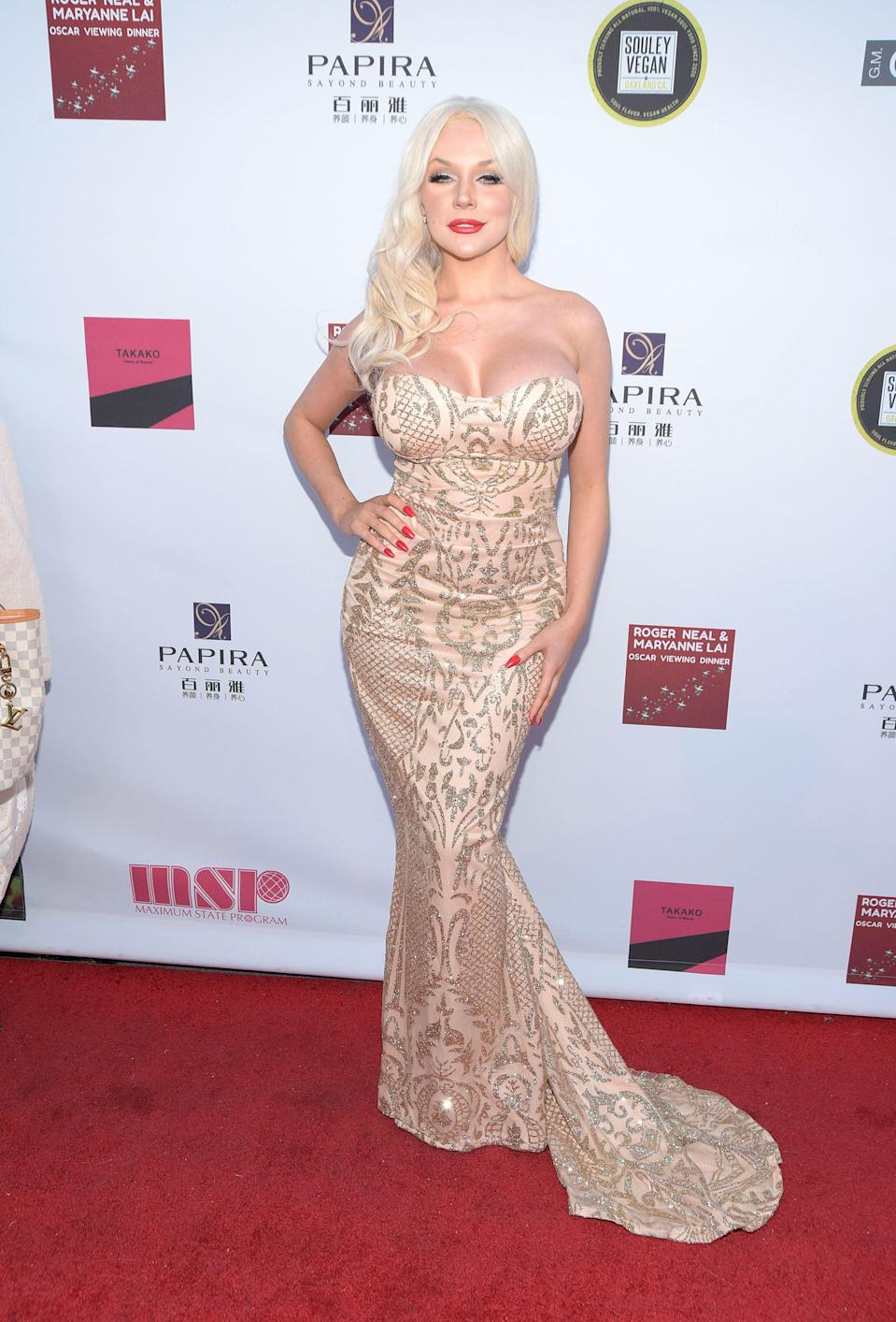 Courtney Stodden looks like a goddess in a gold and shimmery outfit as she poses on the red carpet for the paparazzi to take a few shots.