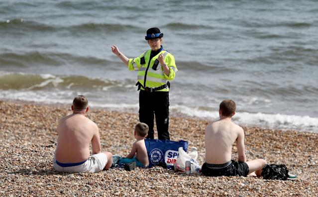 A police officer advises people to leave the beach during the warm weather (Picture: Getty)