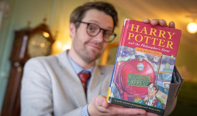 Hansons Auctioneers of Jim Spencer with the first edition Harry Potter book, Harry Potter and the Philosopher's Stone, which was purchased privately for more than $50,000.