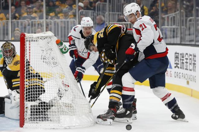 Washington Capitals' Garnet Hathaway (21) and Boston Bruins' Brandon Carlo (25) work for the puck during the second period of an NHL hockey game in Boston, Saturday, Nov. 16, 2019. (AP Photo/Michael Dwyer)