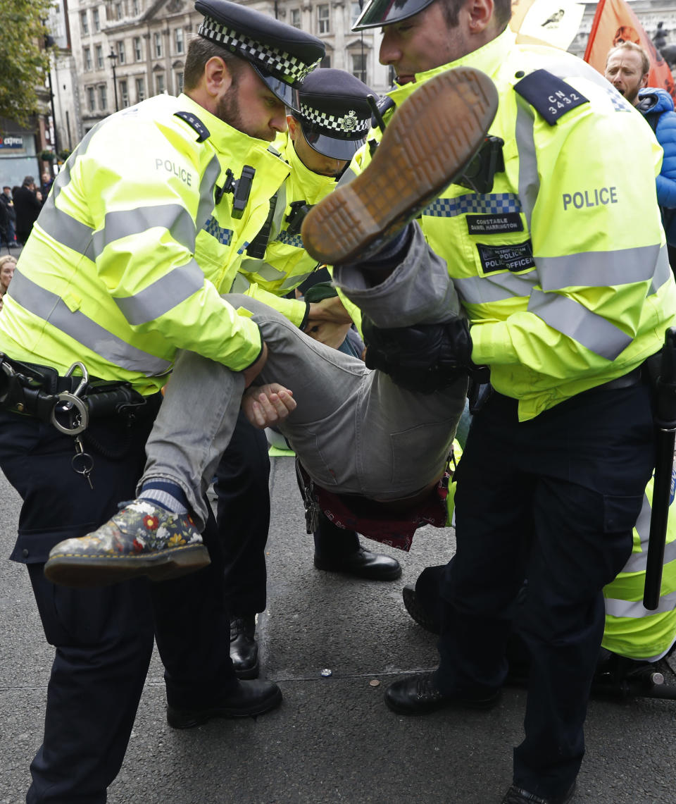 Police arrest a climate protestor after demonstrators blocked Trafalgar Square in central London Monday, Oct. 7, 2019. Extinction Rebellion movement blocked major roads in London, Berlin and Amsterdam on Monday at the beginning of what was billed as a wide-ranging series of protests demanding new climate policies. (AP Photo/Alastair Grant)