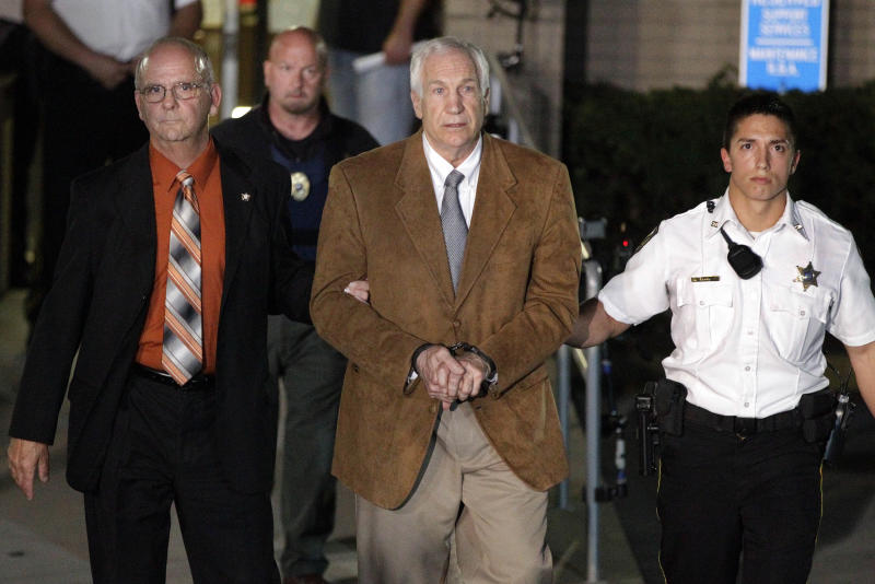 Former Penn State University assistant football coach Jerry Sandusky, center, leaves the Centre County Courthouse in custody with Centre County Sheriff Denny Nau, left, after being found guilty of multiple charges of child sexual abuse in Bellefonte, Pa., Friday, June 22, 2012. Sandusky was convicted of sexually assaulting 10 boys over 15 years, accusations that had sent shock waves through the college campus known as Happy Valley and led to the firing of Penn State's beloved Hall of Fame coach, Joe Paterno. (AP Photo/Gene J. Puskar)