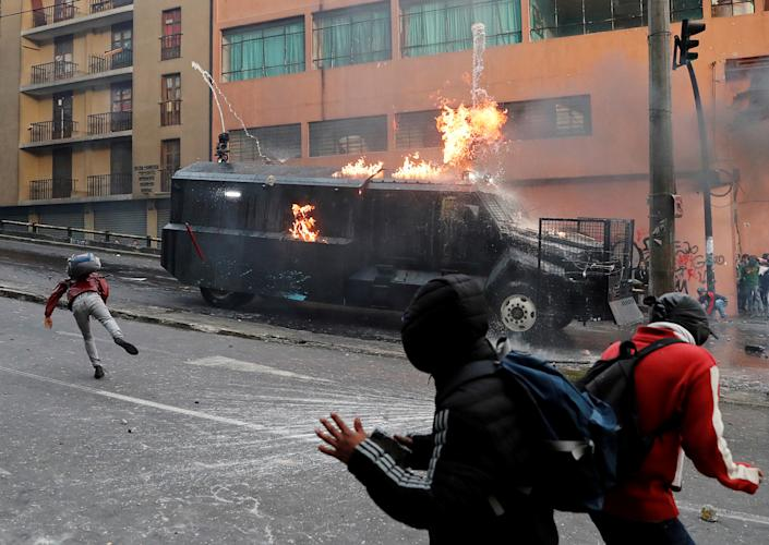 A police vehicle burns during a protest in Ecuador