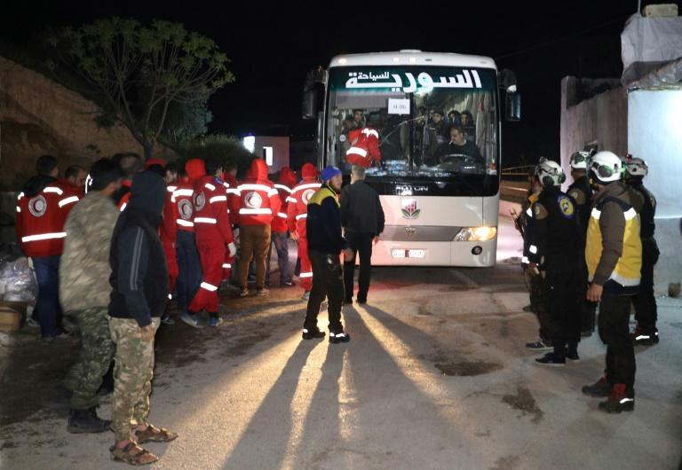 A first convoy evacuating rebel fighters and their families from the Eastern Ghouta enclave outside Damascus reaches the Hama province town of Qalaat al-Madiq where rebels and Red Crescent and White Helmets members await them early on March 23, 2018
