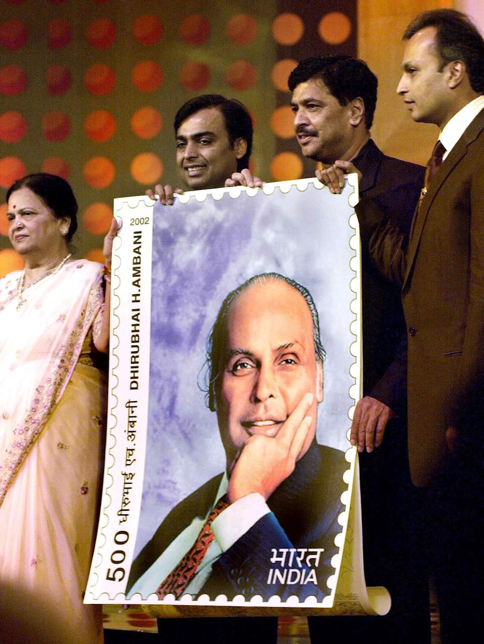 (from L to R) Kokilaben Ambani, Mukes Ambani, Indian Minister for Information and Technology Pramod Mahajan and Anil Ambani pose with a giant postage stamp depicting late founder of Reliance Industries Dhirubhai Ambani in Bombay, 28 December 2002. The stamp was released on the occasion of Dhirubhai Ambani's birthday. AFP PHOTO / Sebastian D'SOUZA