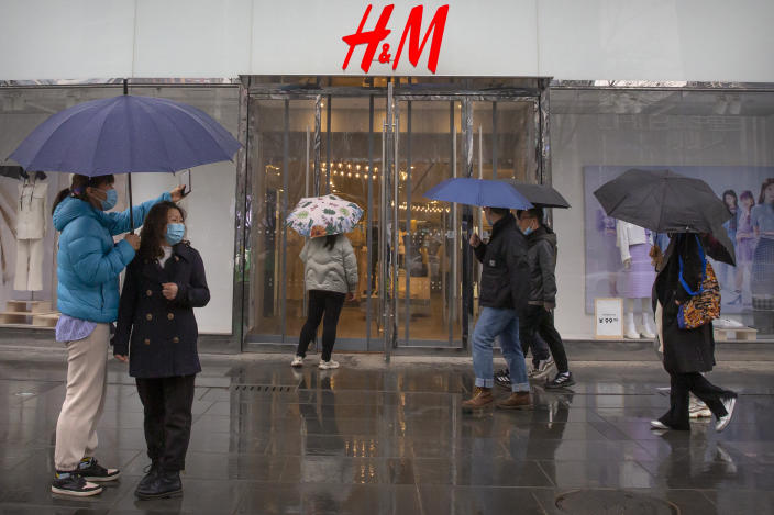 People walk past an H&M clothing store at a shopping mall in Beijing, Friday, March 26, 2021. H&M disappeared from the internet in China as the government raised pressure on shoe and clothing brands and announced sanctions Friday against British officials in a spiraling fight over complaints of abuses in the Xinjiang region. (AP Photo/Mark Schiefelbein)