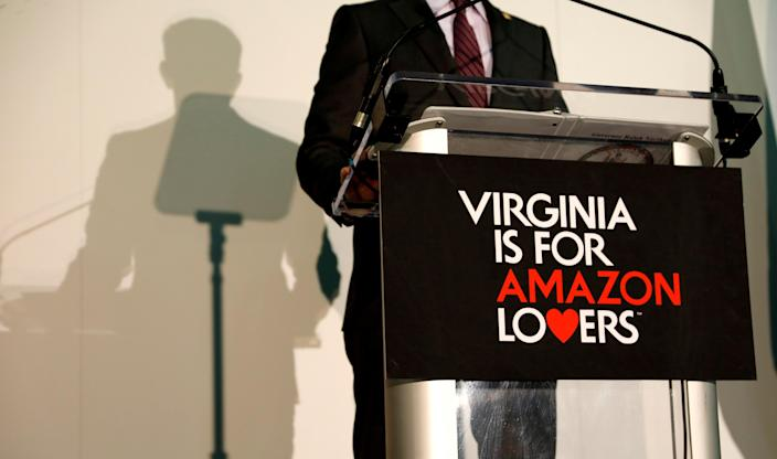 """Behind a """"Virginia is for Amazon Lovers"""" sign, Gov. Ralph Northam speaks at a news conference after Amazon announced Crystal City would be one of its new campuses, Nov.13, 2018. (Photo: Kevin Lamarque/Reuters)"""