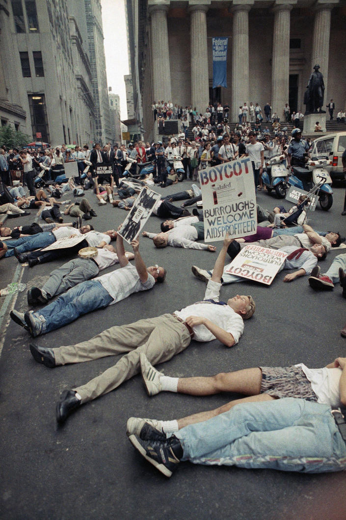 "FILE - In this Thursday, Sept. 14, 1989 file photo, protestors lie on the street in front of the New York Stock Exchange in a demonstration against the high cost of the AIDS treatment drug AZT. The protest was organized by the gay rights activist group ACT UP. In response to protests, the FDA agreed to speed testing and approval of new therapies — a key step in curbing the high death toll from AIDS. Activist Larry Kramer, who died in May, said the protesters' sense of rage made a difference. ""Until you have anger and fear, you don't have any kind of an activist movement,"" he told Metro Weekly, a Washington-based LGBT publication, in 2011. (AP Photo/Tim Clary, File)"