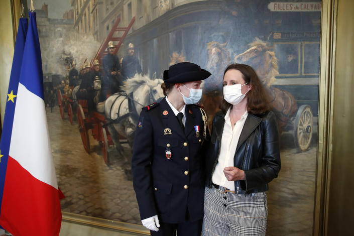 French math teacher-volunteer fighter, Marion Dehecq, left, talks with Paris-based Associated Press journalist Lori Hinnant, after she receives a bronze medal for courage and dedication as she used CPR to save the life of a jogger, during a ceremony with France's minister for citizenship issues, Marlene Schiappa at the Paris fire service headquarters in Paris, France, Monday, May 10, 2021. The jogger's wife, Paris-based Associated Press journalist Lori Hinnant, helped identify the anonymous rescuer by putting up thank-you signs in Monceau Park, where her husband Peter Sigal went into cardiac arrest on April 28. (AP Photo/Francois Mori, pool)