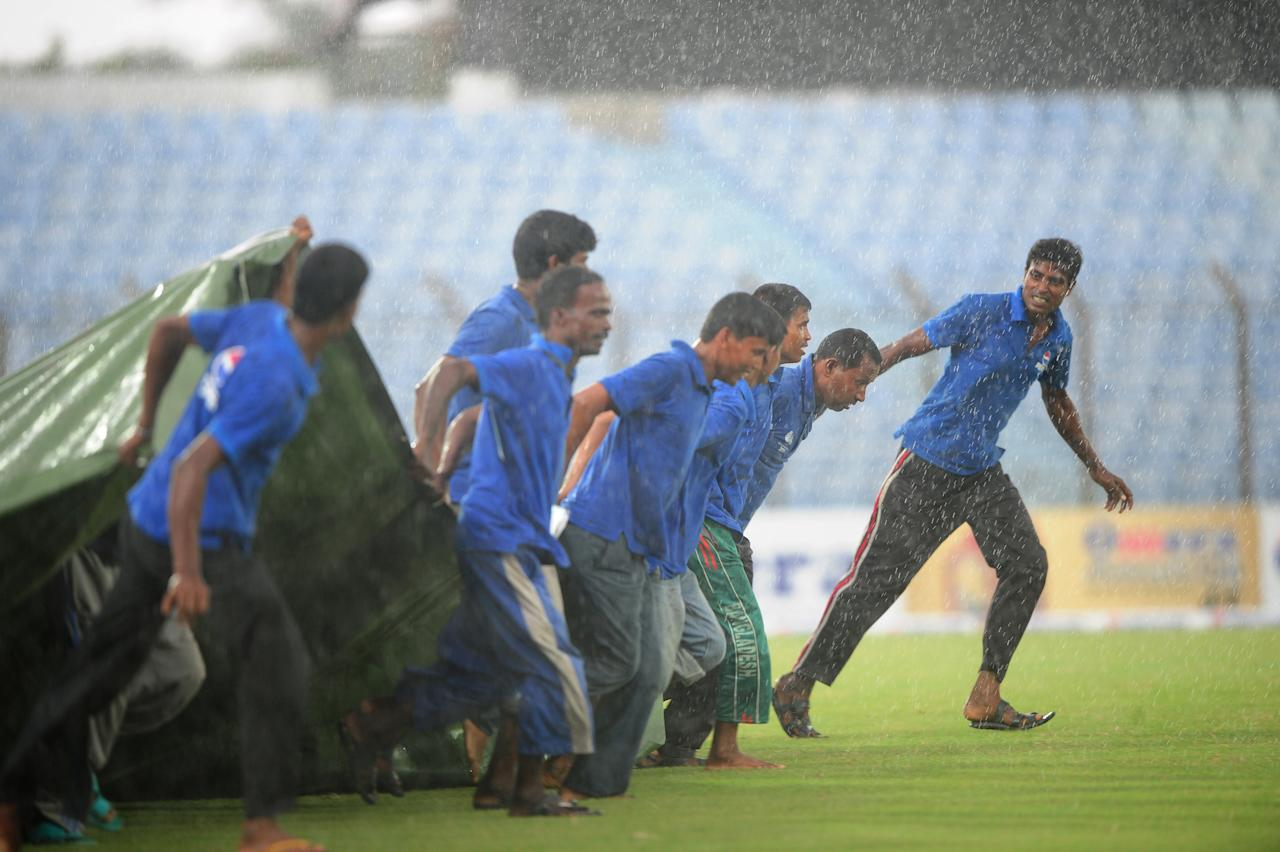 Bangladeshi grounds men cover the pitch during rain on the fourth day of the first cricket Test match between Bangladesh and New Zealand at the Zahur Ahmed Chowdhury Stadium in Chittagong on October 12, 2013. AFP PHOTO/ Munir uz ZAMAN        (Photo credit should read MUNIR UZ ZAMAN/AFP/Getty Images)