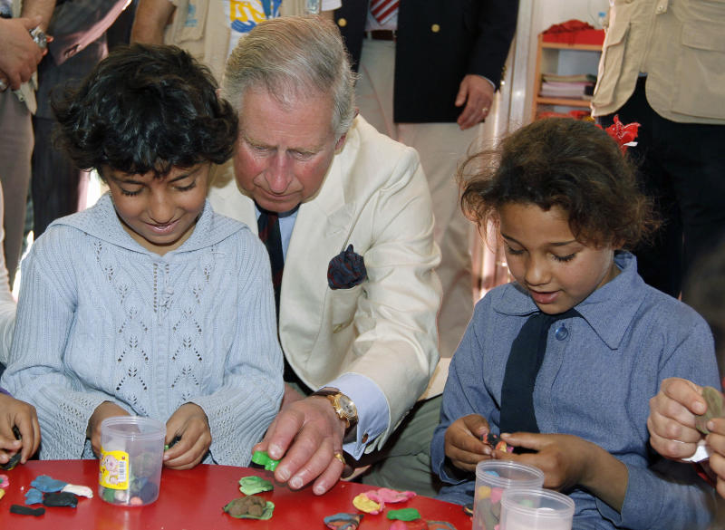 Britain's Prince Charles, center, sits with Syrian refugee children during his visit to the King Abdullah Park for Syrian Refugees in Ramtha city north of Amman, Jordan, Wednesday, March 13, 2013. Prince Charles and his wife Duchess Camilla are in Amman on a three-day official visit. (AP Photo/Jamal Nasrallah, Pool)