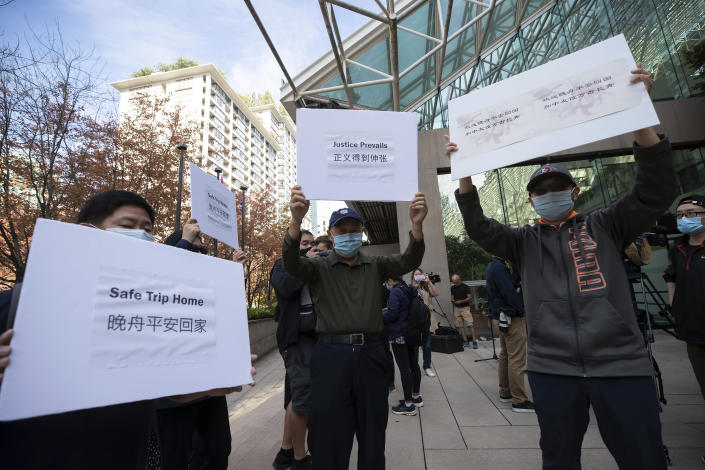 Supporters of Meng Wanzhou, chief financial officer of Huawei, hold signs outside B.C. Supreme Court in Vancouver, British Columbia, Friday, Sept. 24, 2021. (Darryl Dyck/The Canadian Press via AP)