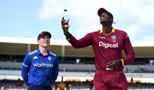 BRIDGETOWN, BARBADOS - MARCH 09: West Indies captain Jason Holder tosses the coin alongside England captain Eoin Morgan ahead of the 3rd One Day International between the West Indies and England at Kensington Oval on March 9, 2017 in Bridgetown, Barbados. (Photo by Gareth Copley/Getty Images)