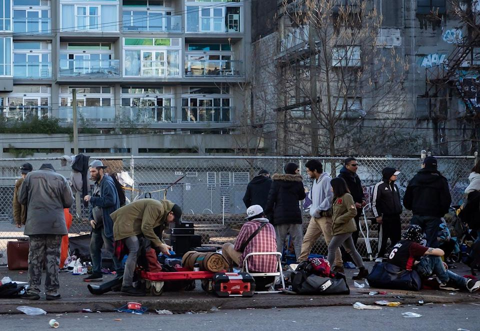 A number of people, including homeless people, gather on a crowded street in Vancouver.