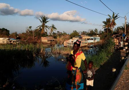 A woman walks with her children past flooded houses in the aftermath of Cyclone Idai in Tica near Beira,