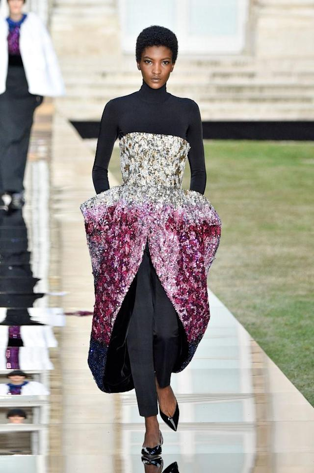 <p>Model wears a long-sleeve shirt and trousers underneath a dazzling multicolored crystal dress from the Givenchy fall 2018 couture collection. (Photo: Getty Images) </p>