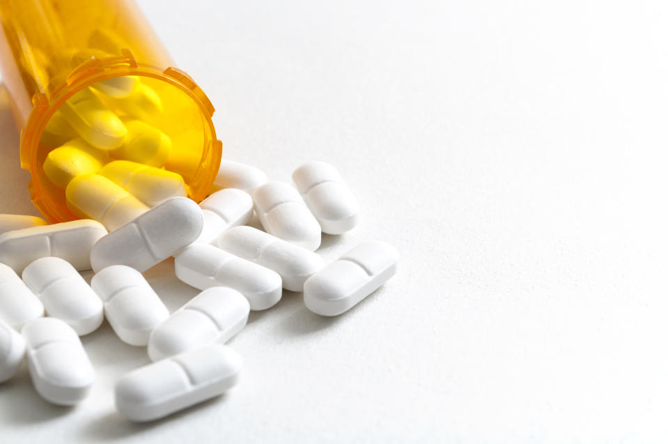 Opioid epidemic, drug abuse and overdose concept with scattered prescription opioids spilling from orange bottle with copy space. Hydrocodone is the generic name for a range of opiate painkillers