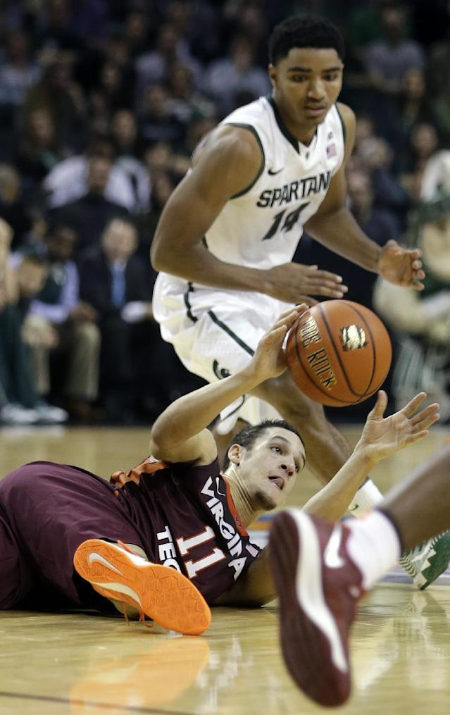 Virginia Tech's Devin Wilson (11) passes the ball away from Michigan State's Gary Harris (14) during the first half of a Coaches vs. Cancer NCAA college basketball game on Friday, Nov. 22, 2013, in New York. (AP Photo/Frank Franklin II)