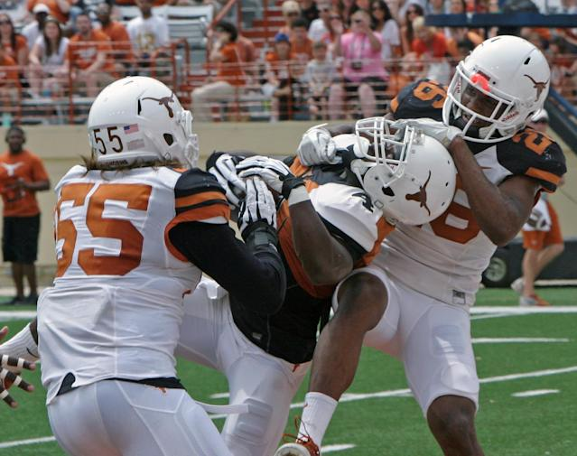 Texas running back Daje Johnson (4) pulls down a pass for a touchdown against Dalton Santos (55) and Adrian Colbert (26) during the first half of the Orange and White spring NCAA college football game, Saturday, April 19, 2014, in Austin, Texas. (AP Photo/Michael Thomas)