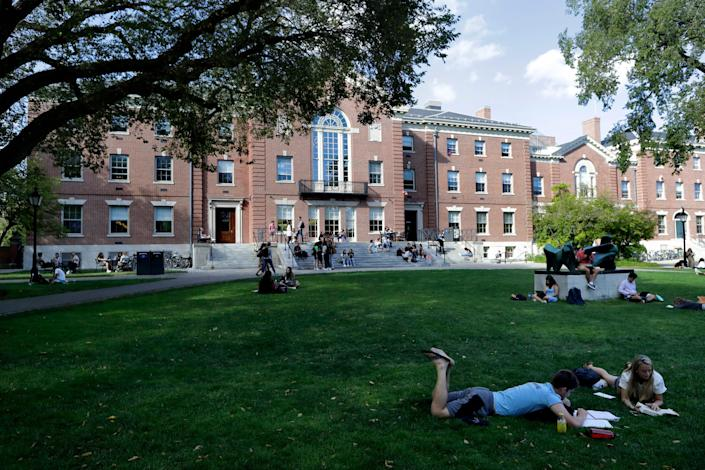 People rest on grass while reading at Brown University in Providence, R.I., in September 2019.