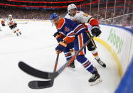 Calgary Flames' Derek Ryan (10) and Edmonton Oilers' Kris Russell (4) battle for the puck during first period NHL action in Edmonton on Sunday, Dec. 9, 2018. (Jason Franson/The Canadian Press via AP)