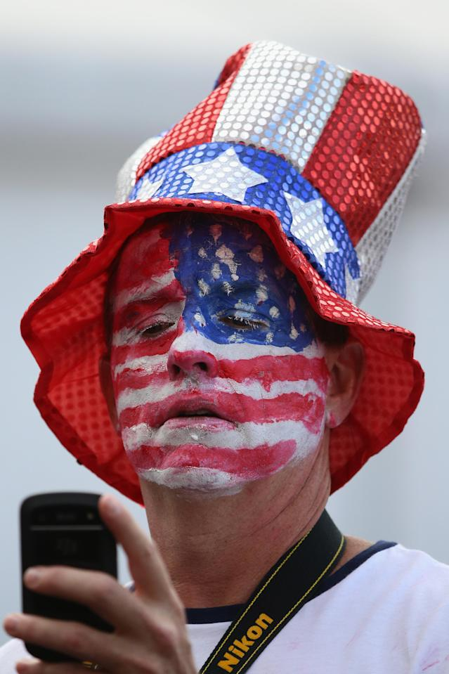 LONDON, ENGLAND - JULY 29: A man with an American flag painted on his face takes a photograph on his phone at the Olympic Park on Day 2 of the London 2012 Olympic Games on July 29, 2012 in London, England. (Photo by Jeff J Mitchell/Getty Images)