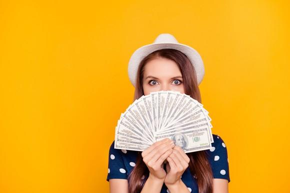 A woman in a blue shirt and white hat stands against a yellow background, holding a fanned-out pile of hundred-dollar bills in front of her face.