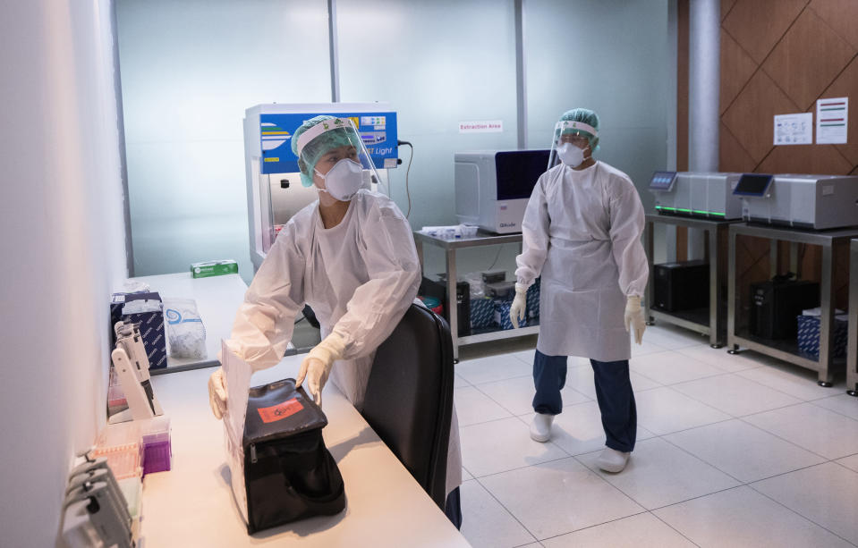 Laboratory staff members work for the COVID-19 virus testing at Suvarnabhumi Airport in Bangkok, Friday, July 3, 2020. As the country starts to ease its travel restrictions allowing foreign visitors in on a controlled basis, the lab will have the results ready within 90 minutes for arriving travelers. (AP Photo/Sakchai Lalit)