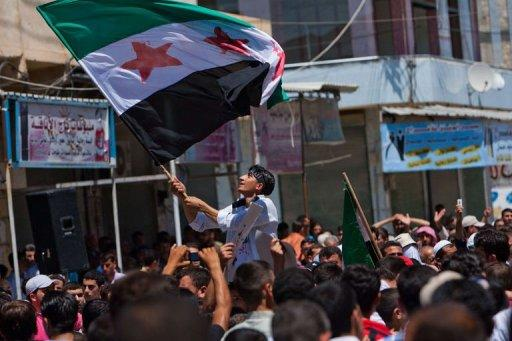 A Syrian youth waves the Syrian revolutionary flag during an anti-government demonstration after Friday prayers in the rebel-controlled northern countryside city of Mareh. Russia reported finding agreement with the United States on Syria and voiced optimism that crucial Geneva talks Saturday could bring a shift toward peace after 16 months of bloodshed