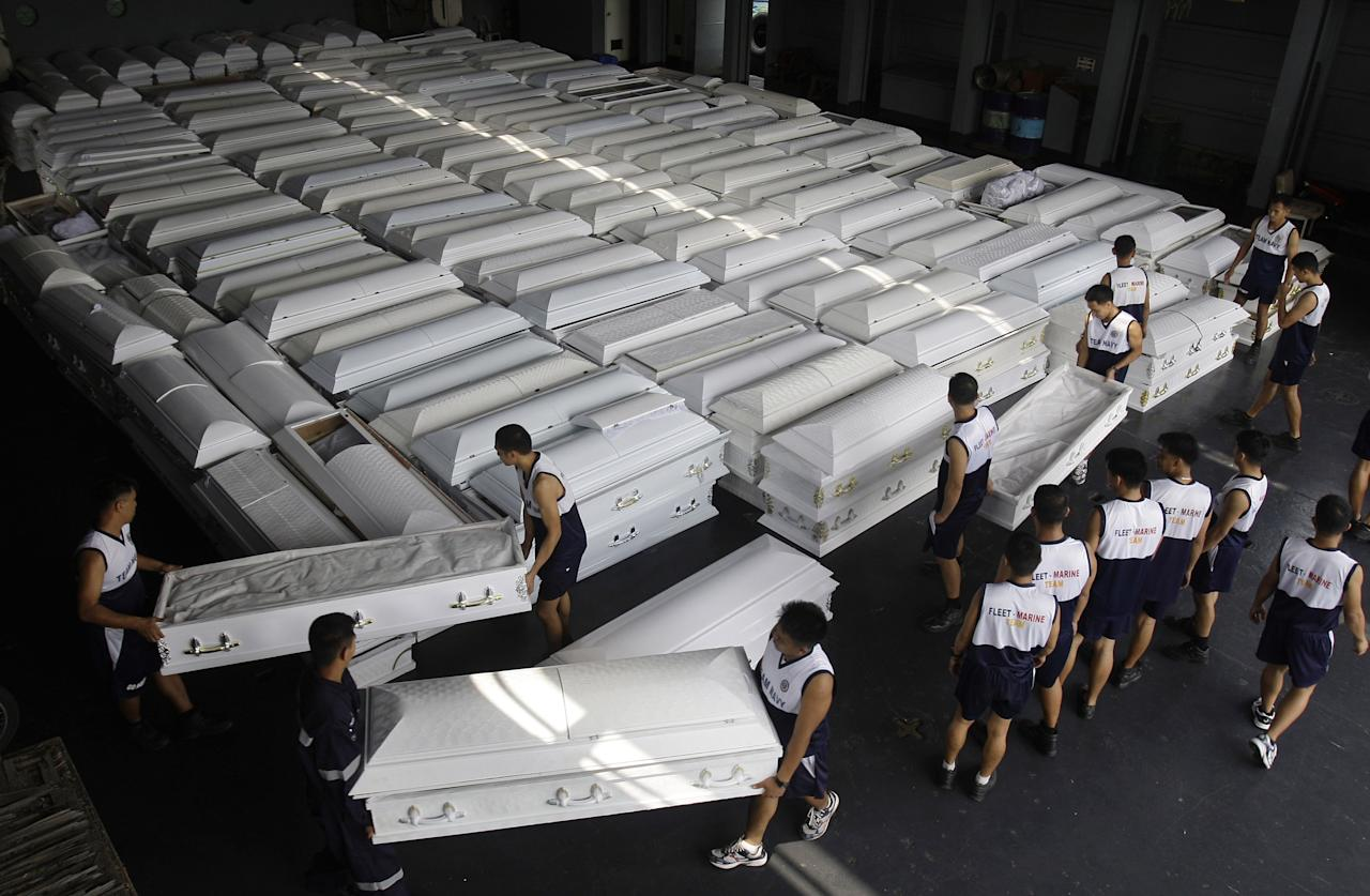Philippine Navy personnel carry coffins that will be shipped with drinking water, clothes and other relief goods to flood-stricken Cagayan De Oro and Iligan cities on board a Philippine Navy ship in Manila, Philippines on Tuesday Dec. 20, 2011. Nearly a thousand people died in massive flash floods when tropical storm Washi hit the country last week in one of the worst disasters to strike the region in decades. (AP Photo/Aaron Favila)
