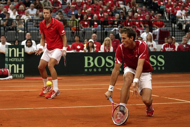 Canada's Vasek Pospisil, right, returns a ball as Daniel Nestor, his doubles partner, looks on during their Davis Cup semifinals tennis doubles match against Serbia's Nenad Zimonjic and Ilija Bozoljac in Belgrade, Serbia, Saturday, Sept. 14, 2013. (AP Photo/Marko Drobnjakovic)