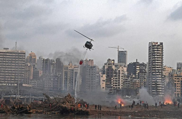 A helicopter tries to put out multiple fires at the scene of the massive explosion that hit Beirut's port on August 4, 2020
