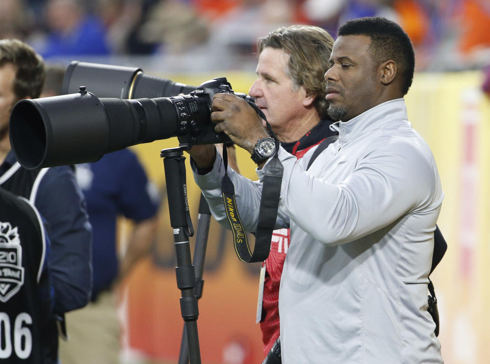 Former MLB baseball player Ken Griffey Jr. shoots pictures from the sidelines during the first half of the Fiesta Bowl NCAA college football game between Arizona and Boise State, Wednesday, Dec. 31, 2014, in Glendale, Ariz. (AP Photo/Ross D. Franklin)