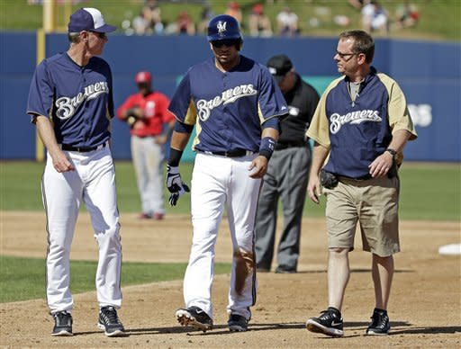 Milwaukee Brewers manager Ron Roenicke, left, watches as Aramis Ramirez, center, is escorted off the field after injuring himself after hitting a double during the third inning of an exhibition spring training baseball game against the Los Angeles Angels, Saturday, March 2, 2013, in Phoenix. (AP Photo/Morry Gash)