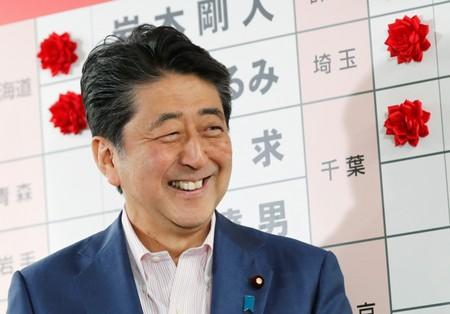 Japan's Prime Minister Shinzo Abe, who is also leader of the ruling Liberal Democratic Party (LDP), reacts as he puts a rosette on the name of a candidate who is expected to win the upper house election, at the LDP headquarters in Tokyo