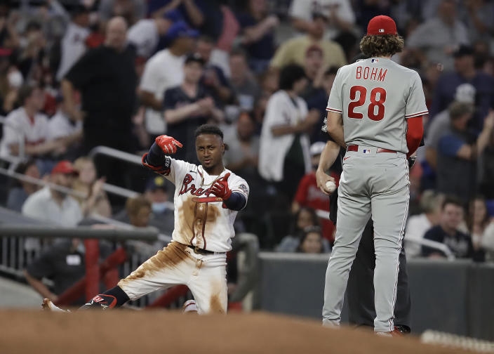 Atlanta Braves' Ozzie Albies, left, celebrates beside Philadelphia Phillies third baseman Alec Bohm (28) after hitting a triple in the fourth inning of a baseball game Saturday, May 8, 2021, in Atlanta. (AP Photo/Ben Margot)