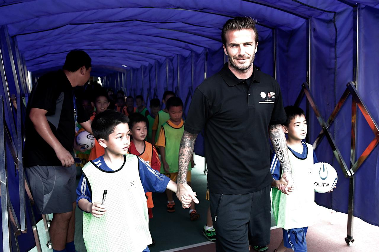 BEIJING, CHINA - JUNE 18: David Beckham walks with young fans at Nanjing Olympic Sports Center on June 18, 2013 in Nanjing, Jiangsu Province of China. (Photo by Lintao Zhang/Getty Images)