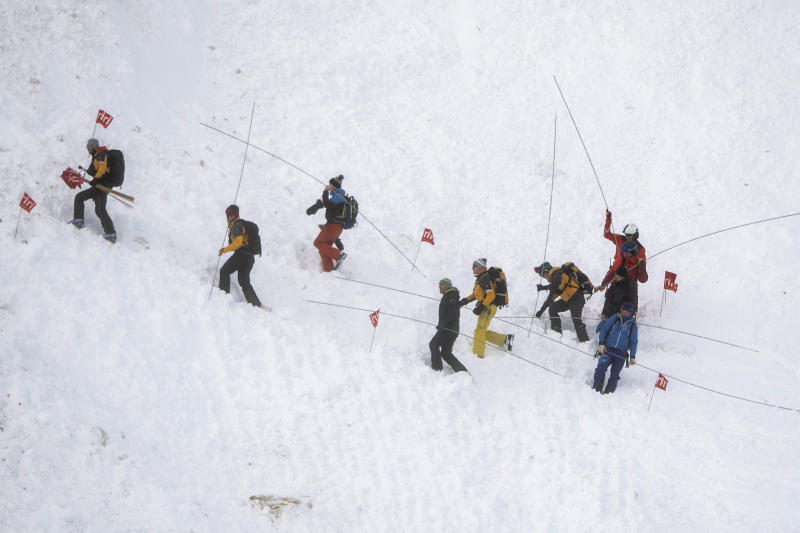 Rescue forces search for missing people after an avalanche swept down a ski piste in the central town of Andermatt, canton Uri, Switzerland, Thursday, Dec. 26, 2019. The avalanche occurred mid-morning Thursday while many holiday skiers enjoyed mountain sunshine the day after Christmas. (Urs Flueeler/Keystone via AP)