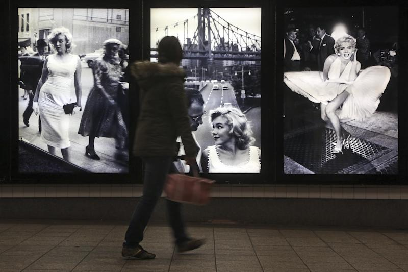 """A commuter inspects the Sam Shaw's photographs during the """"Marilyn in New York"""" exhibit at the 42nd St. subway station for the B,D,F,M and 7 lines, Thursday, Dec. 20, 2012 in New York. The exhibit is part of the Metropolitan Transportation Authority's """"Arts for Transit"""" program. The show opened Thursday and will be up for a year. (AP Photo/Mary Altaffer)"""