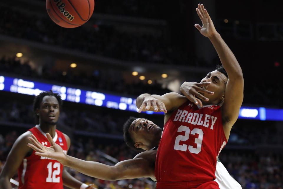 <p>Michigan State forward Xavier Tillman, center, fights for a loose ball with Bradley guard Dwayne Lautier-Ogunleye (23) during a first round men's college basketball game in the NCAA Tournament, Thursday, March 21, 2019, in Des Moines, Iowa. (AP Photo/Charlie Neibergall) </p>