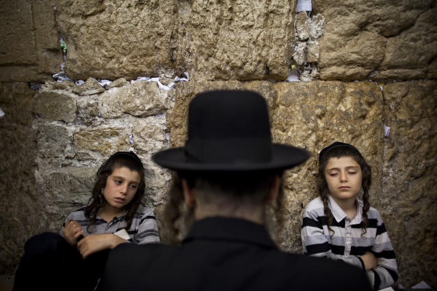 <p>Ultra-Orthodox Jewish men pray as they gather for the mourning ritual of Tisha B'Av at the Western Wall, the holiest site where Jews can pray, in Jerusalem's Old City, July 29, 2012. (Photo: Oded Balilty/AP) </p>