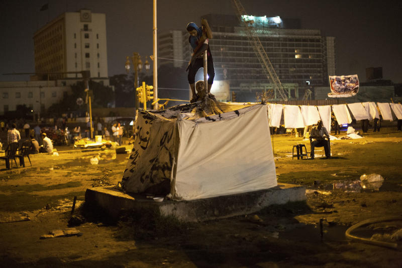 FILE - In this Thursday, June 27, 2013 file photo, Egyptian men build up a tent in Tahrir Square in Cairo. Cairo is bracing for mass protests against the government planned for Sunday. As the streets once again fill with protesters eager to oust the president and Islamists determined to keep him in power, Egyptians are preparing for the worst: days or weeks of urban chaos that could turn a loved one into a victim. Households already beset by power cuts, fuel shortages and rising prices are stocking up on goods in case the demonstrations drag on. Businesses near protest sites are closing until crowds subside. Fences, barricades and walls are going up near homes and key buildings. And local communities are organizing citizen patrols in case security breaks down. (AP Photo/Manu Brabo)