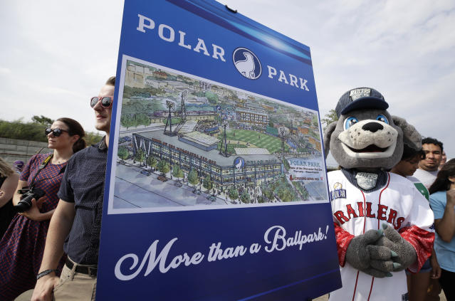 Spectators watch near an artist's rendering during a groundbreaking ceremony for a new minor league baseball stadium, Thursday, July 11, 2019, in Worcester, Mass. Polar Park will be the new home of the Boston Red Sox' Triple-A affiliate, beginning in 2021. The club announced last year that it is moving from Pawtucket, R.I. to Worcester after failing to reach a deal for a new stadium with Rhode Island officials. (AP Photo/Elise Amendola)