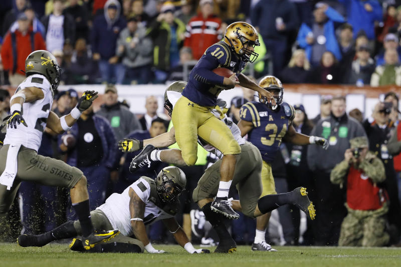 Navy's Malcolm Perry (10) leaps over Army's Donavan Lynch (11) during the second half of an NCAA college football game, Saturday, Dec. 14, 2019, in Philadelphia. (AP Photo/Matt Slocum)