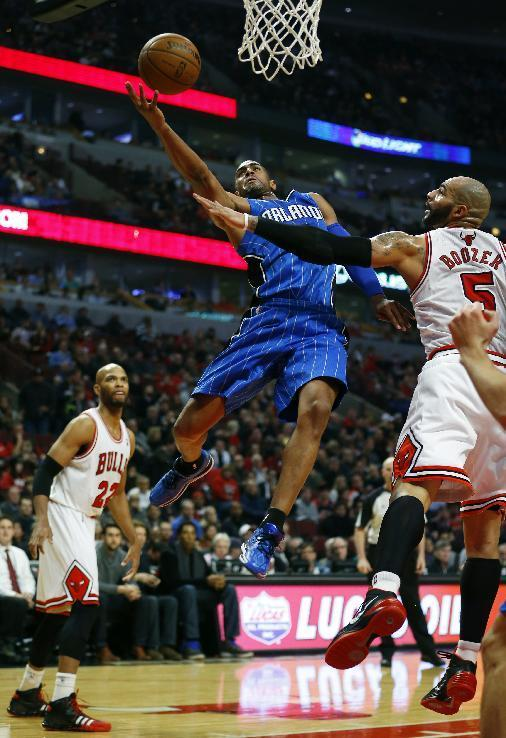 Orlando Magic shooting guard Arron Afflalo, center, goes to the basket between Chicago Bulls forward Taj Gibson, left, and forward Carlos Boozer, right, during the first half of an NBA basketball game in Chicago on Monday, Dec. 16, 2013. (AP Photo/Jeff Haynes)