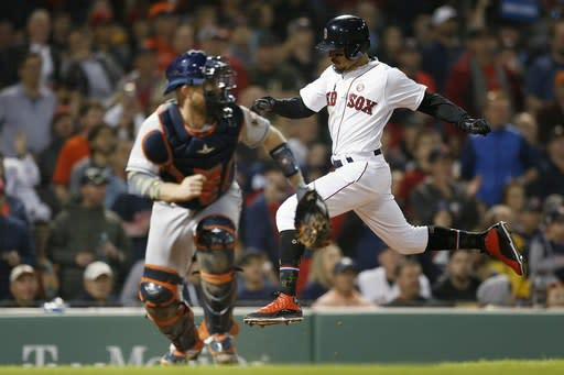 Boston Red Sox's Mookie Betts, right, scores on a double by Mitch Moreland as Houston Astros' Max Stassi looks for the throw during the third inning of a baseball game in Boston, Saturday, May 18, 2019. (AP Photo/Michael Dwyer)