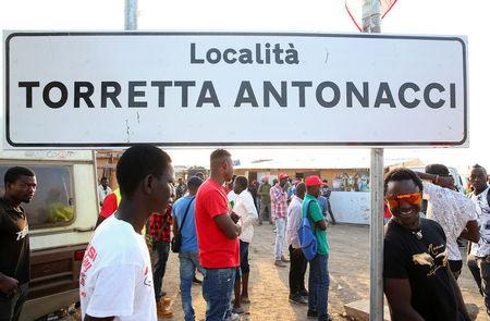 """African migrant labourers stand near a road sign reading """"Torretta Antonacci place"""" outside their camp, known as the """"Great Ghetto"""", near Foggia, Italy August 8, 2018. Picture taken August 8, 2018.    REUTERS/Alessandro Bianchi"""