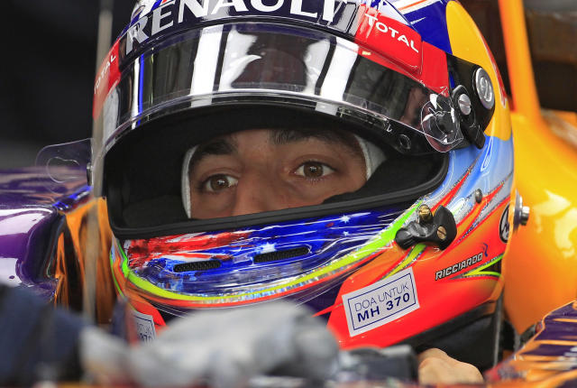 "A sticker reads ""Pray for MH370"" is pasted on the helmet of Red Bull Racing driver Daniel Ricciardo of Australia as he prepares for the first practice session ahead of Sunday's Malaysian Formula One Grand Prix at Sepang International Circuit in Sepang, Malaysia, Friday, March 28, 2014. (AP Photo/Lai Seng Sin)"