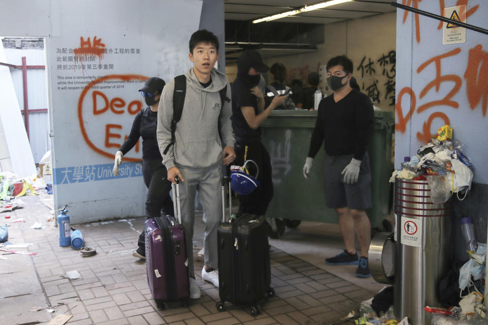 A student pushes his luggage past pro-democracy protesters as he leaves the Chinese University of Hong Kong following a clash in Hong Kong, Wednesday, Nov. 13, 2019. University students from mainland China are fleeing Hong Kong, and classes for primary and secondary school students have been suspended as attacks and clashes turn increasingly violent in the city's five-month long anti-government unrest. (AP Photo/Kin Cheung)